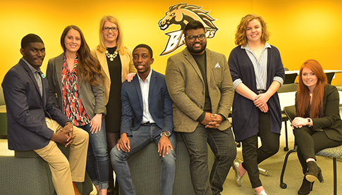 Group of students posing in front of a WMU Bronco logo