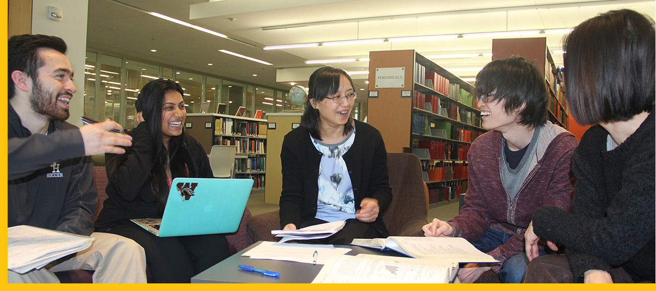 A group of five students sits arond a small table that is filled with papers, books, and notebooks.  They are having a fun discussion and you can see the library bookshelves behind them.