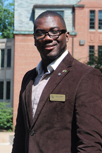 This is a photo of Damon Chambers standing outside of Walwood Hall where the Graduate College and the Graduate Student Association offices are located at W M U. Mr. Chambers is wearing a dark brown courderoy sport coat and dress shirt.  He has short black hair and is wearing dark rimmed glasses and has a welcoming smile