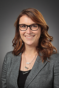 This is a photo of Dr. Rebecca Sametz. Dr. Sametz is wearing a charcoal blazer with a black top and a silver neclace with three chains that each have a rectangular bead in the center of each chain. She has long reddish brown hair that passes a couple inches past her shoulders. She is wearing dark rimmed glasses and has a welcoming smile