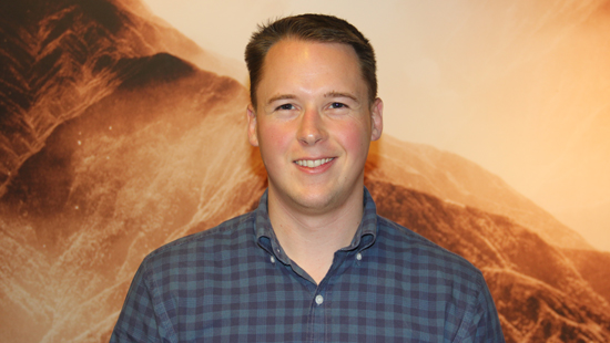 This photo of Rowan Cole shows him standing in Wellborn hall in front of a large sepia-toned landscape photo. Rowan has short brown hair and is clean shaven, he is wearing a blue plaid shirt and a welcoming smile.