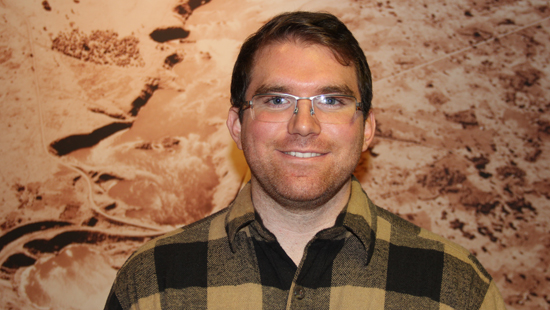 This photo of Trenton Benedict shows him standing in Welborn hall in front of a large sepia-toned landscape photo.  Trenton has short brown hair and is wearing glasses and a plaid shirt with a large brown and tan pattern on it.