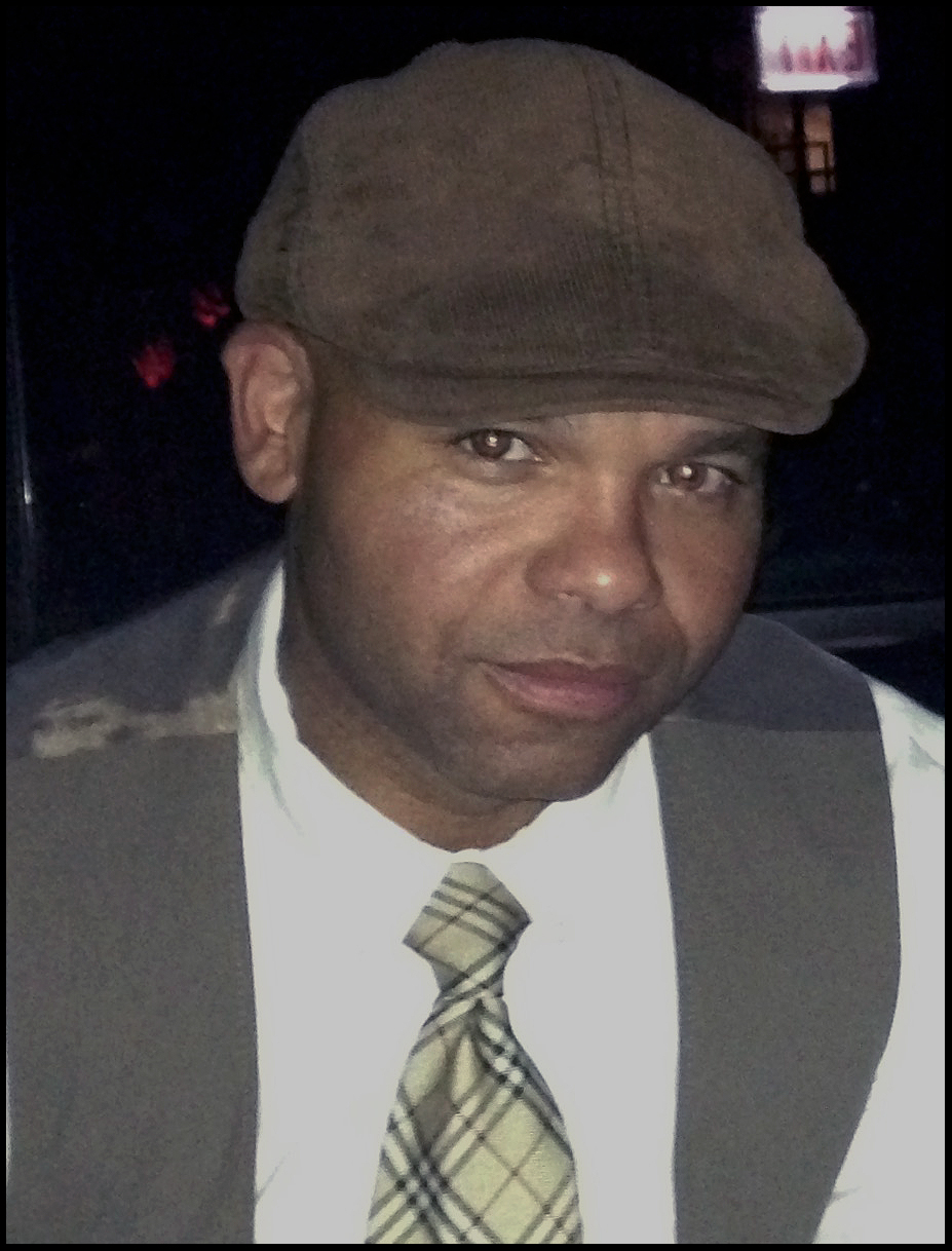 a photo of Ben Williams.  Ben is dressed in a white shirt and monochromatic brown plaid tie with a light brown vest and a light brown corduroy cap that matches the vest in color but offers a different texture.
