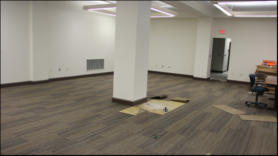 a photo of the main room of the first floor of Walwood hall. The room has been repainted and most of the carpet has been put in.  The carpet is made up of large square tiles that are placed on the floor with adhesive. The places that aren't yet completed are where the tiles have to be cut to fit around pillars, floor vents, or electrical fixtures that can't be moved.