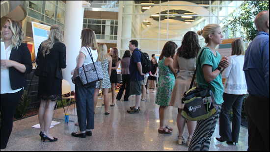 a photo of the crowd attending the Occupational Therapy Poster Day event. The posters are displayed on easels around the perimeter of the atrium area of the College of Health and Human Services at Western Michigan University. The event is well attended with visitors milling around the displays and students on hand to answer questions about their research.