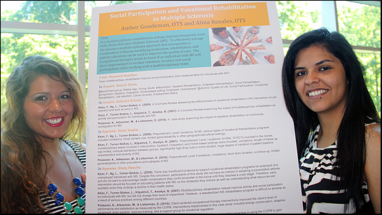 a photo of Occupational Therapy students Amber Goodeman and Alma Rosales standing on each side of their poster presentation titled Social Participation and Vocational Rehabilitation in Multiple Sclerosis.  Amber is on the left and Alma is on the right, the poster is mounted on a foam board and is displayed on an easel for eye-level viewing.