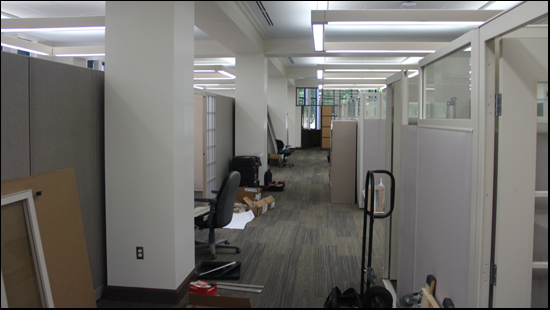 a photo of the main room of the first floor of Walwood hall. The room is once again filled with assembled cubicles, but these cubicles have recently been recycled from another area and look almost new.  Everything is bright and shiny, but a few pieces still need to be put in place and so there are various parts lining the halls.