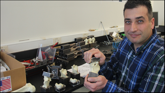 This photo of Saif shows him in his lab seated at a lab bench. He is holding the same engineered bone sample as the first picture, but on the bench beside him are five more samples, one that is complete and four that have been broken due to the stress testing. Saif has short dark hair. He is wearing a blue and white plad patterned shirt.