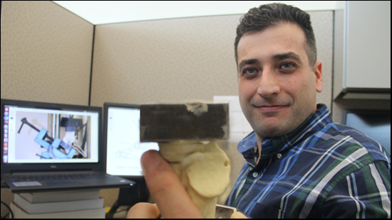 a photo of Saif Alrafeek. Saif is holding a piece of engineered bone which has square metal plates attached on each end. Different bone repair materials will be attached to the bone, and then the sample will be stress tested with pulling and or crushing forces. The best repair materials may go on to be used in surgery repair with real bones. Saif is in his office in this photo, sitting in front of his computer which has mechanical engineering information about his project on the display screens.