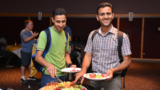 a photo of two international graduate students enjoying the food at the fall welcome