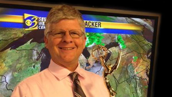 a photo of Emmy award winning Channel 3 weatherman and recent W M U graduate Keith Thompson.  In this photo Mr. Thompson poses in front of a satellite-weather-display screen with his Emmy award.