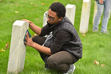 Student cleaning headstone