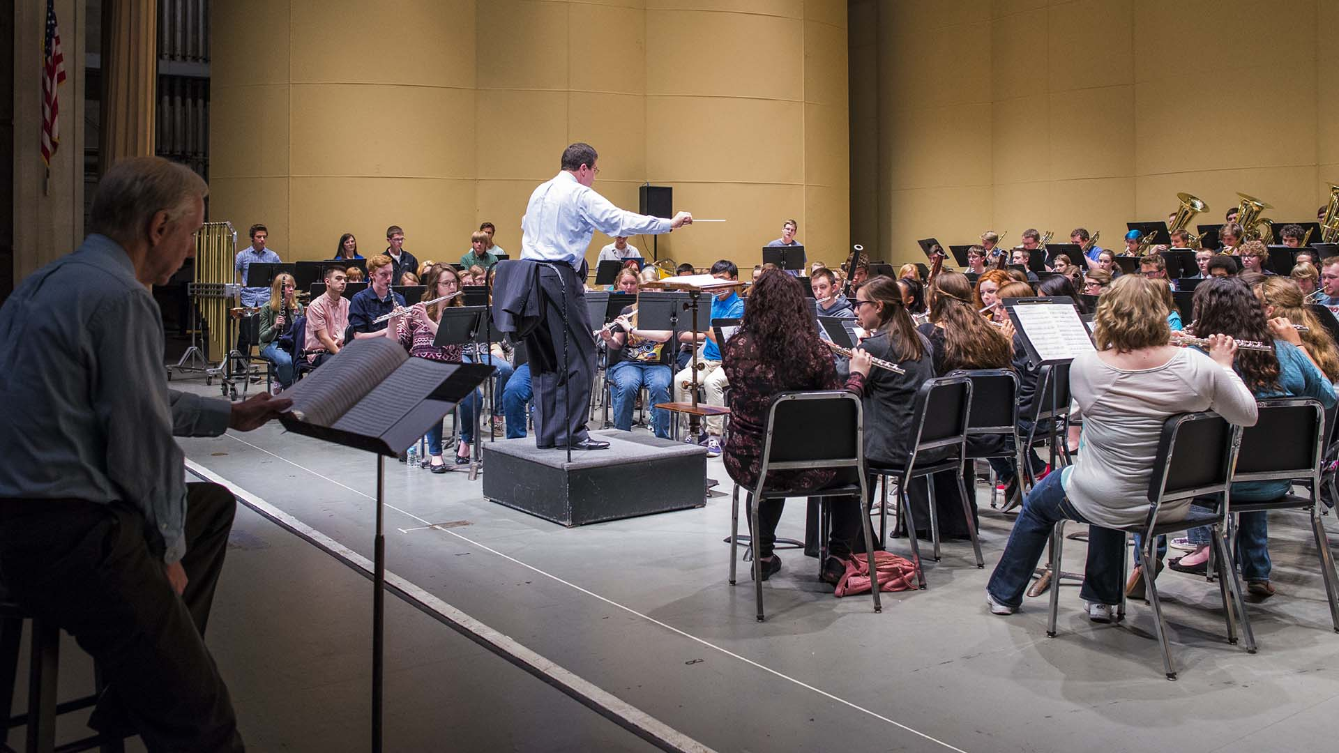Spring Conference All-Star Band rehearsing with guest composer following the score seated on stage