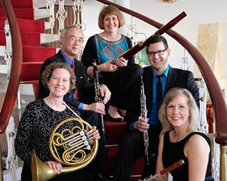 Picture of Western Wind Quintet comprised of female flutist, horn player, bassoonist, and male clarinetist and oboist sitting on a spiral staircase