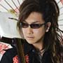 headshot photograph of Japanese musician Sato Michiyoshi wearing all black with small black sunglasses holding a shamisen