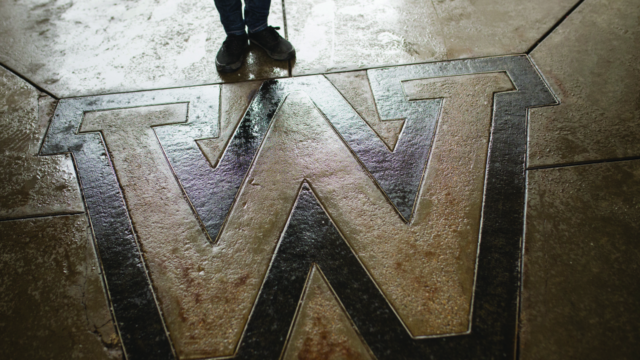 Person standing near the W on campus.
