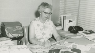 Librarian Jean Lowrie sitting at her desk and looking at a paper circa 1964.
