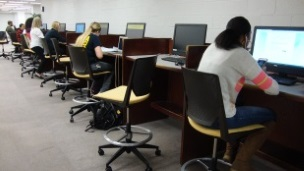 Students sitting at computer workstations in the library.