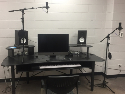 Studio featuring computer, speakers, microphone and piano keyboard.
