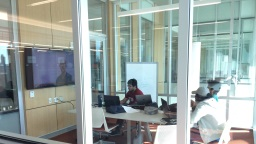 Three students sitting in a group study room at Swain Education Library looking at a large monitor hanging on the wall.