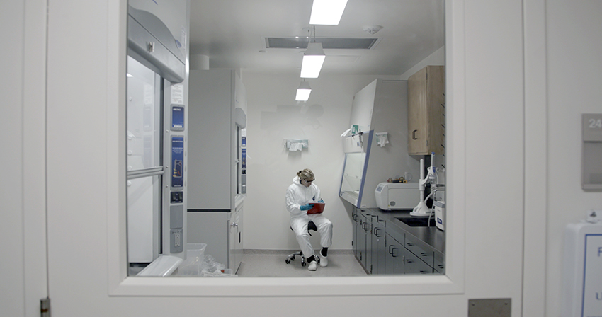 A female scientist sitting on a chair entering data in a lab from behind a closed door.