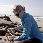 Female scientist at a beach excavating items from the sane.