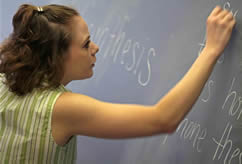 Student writing on a chalkboard.