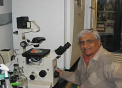 Dr. Essani posing in front of a microscope