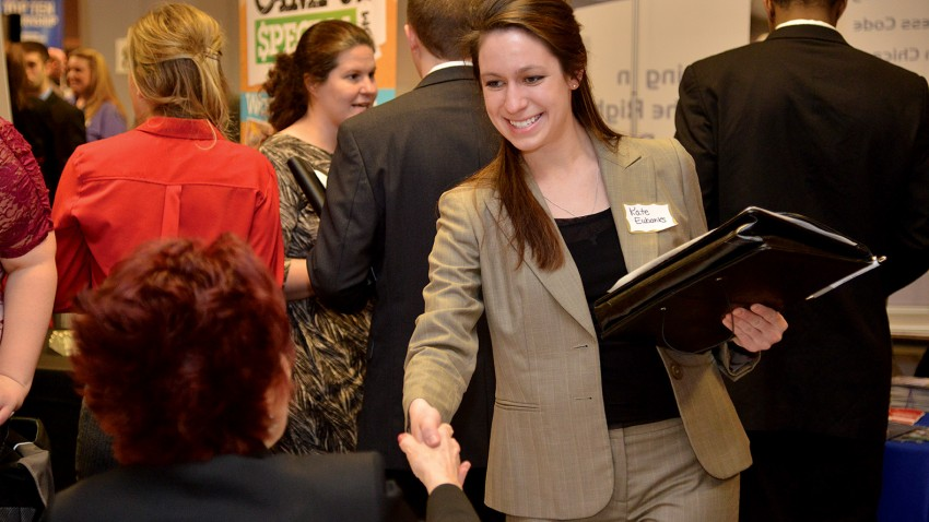 A smiling student shaking an employer's hand