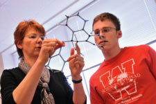 Teacher showing student a molecule model.