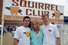 Three students standing in from of squirrel club banner.