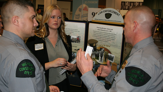 Student talking to conservation officers at career fair