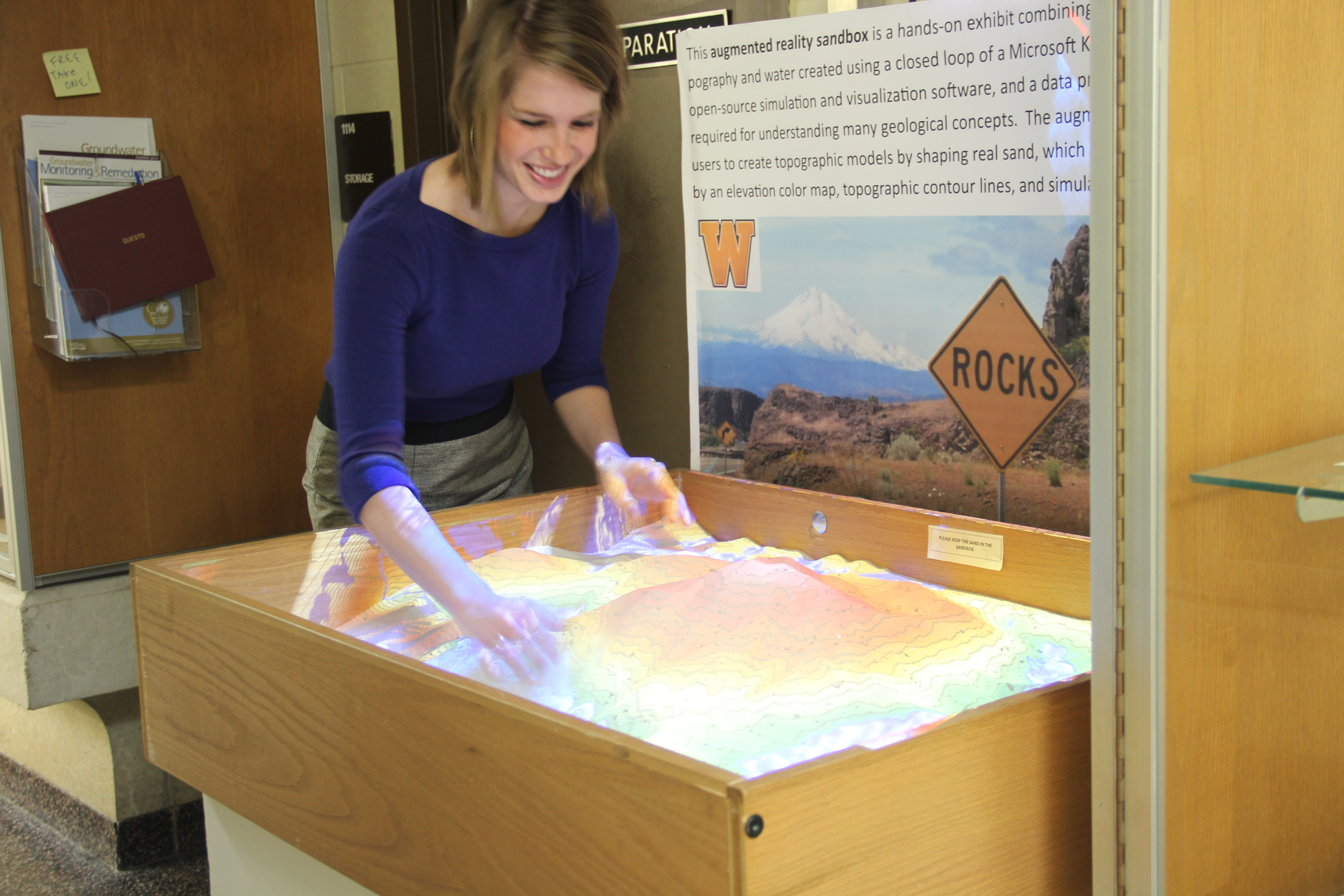 This photo shows Sara VanderMeer interacting with an exhibit in Rood Hall. The exhibit consists of a table that's roughly two feet in width by three feet in length that makes a raised sand box about a foot deep. In the box is a great deal of sand that the visitor can move around with a small scoop. The interesting thing about the exhibit is that it's lit from above with colored lights, and somehow the lights sense the height of the sand and color the sand in different colors according to how high it is piled within the box. This creates a three dimensional representation of a topographical map, and it's fun because one can change the map to one's liking.