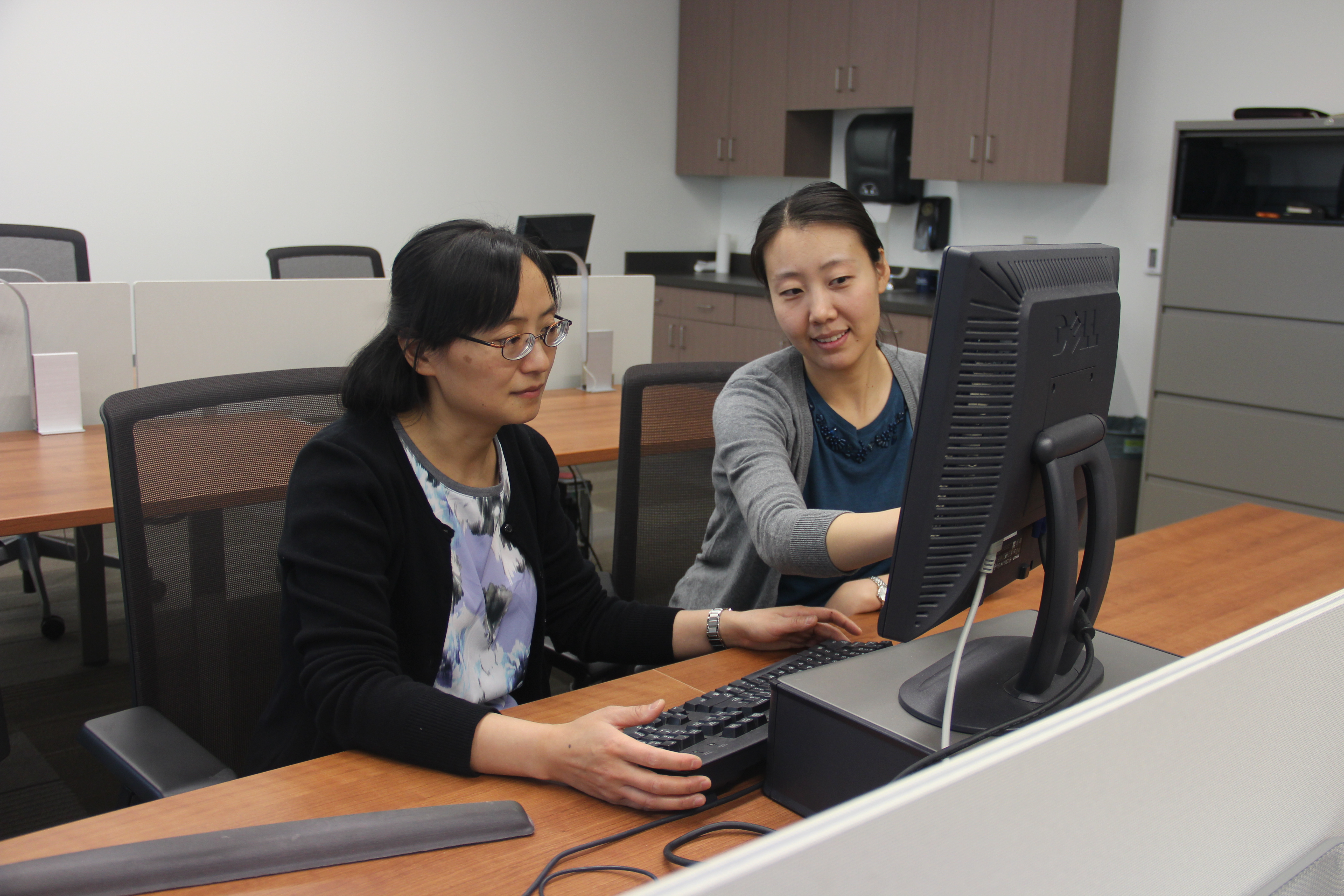 In this photo Yu Du and a friend are in a lab togehter sharing a computer screen. Her friend points to a detail on the screen as Yu looks on.