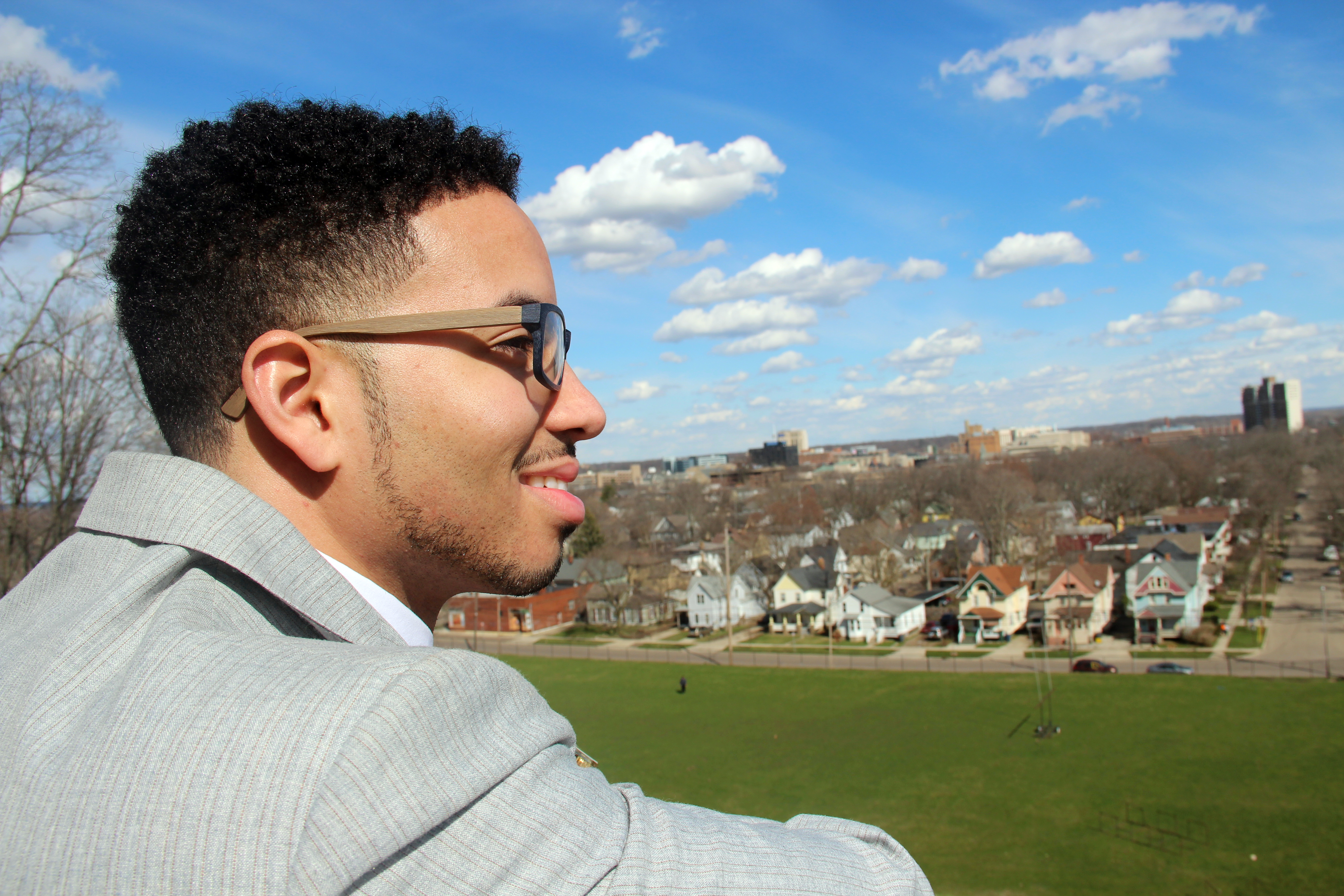 In this photo Javon Dobbs is on the back wall behind Heritage Hall looking out over the Kalamazoo valley The sun shines on his smiling face and the green of the lacross field stretches out below. Behind the field little rows of orderly houses line the streets of the Vine neighborhood.