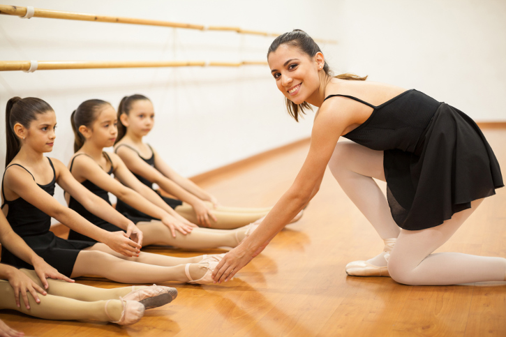 dance teacher and students stretching in studio