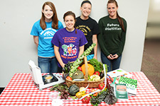 Dietetic students in front of fruits and vegetables.