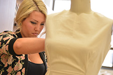 A student uses a mannequin to help with creating a piece of clothing.