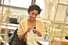 A student sews clothing.