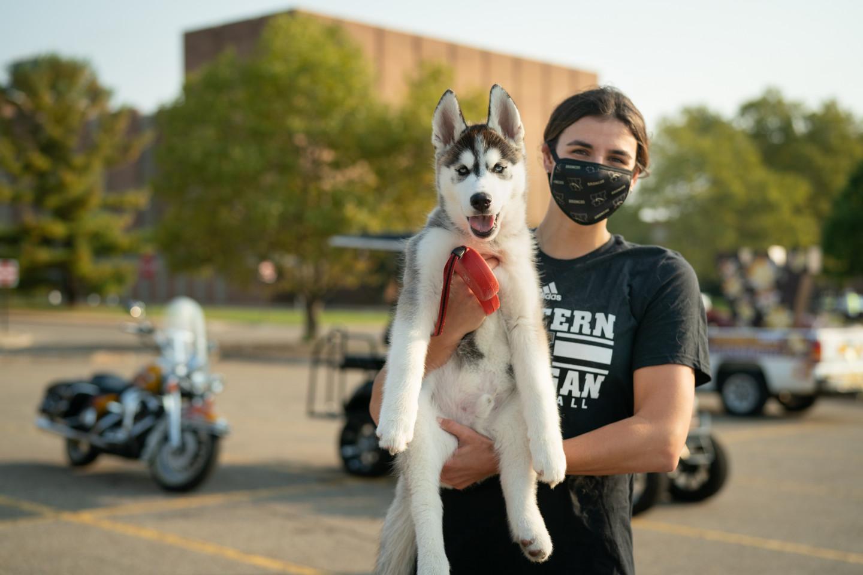 A student holds a husky puppy.