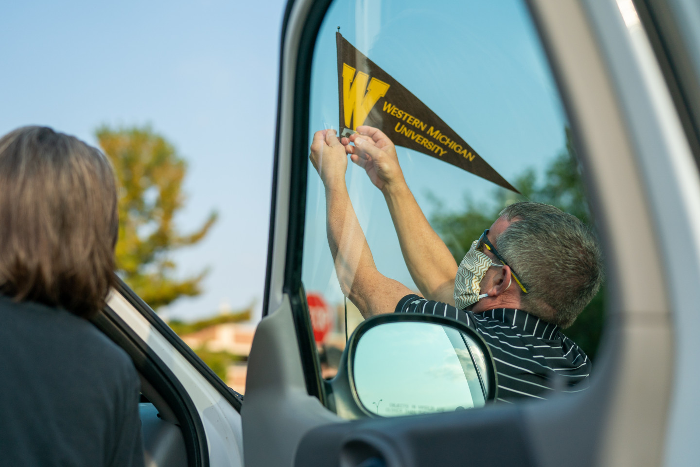A person puts a Western Michigan University pennant on his car antenna.