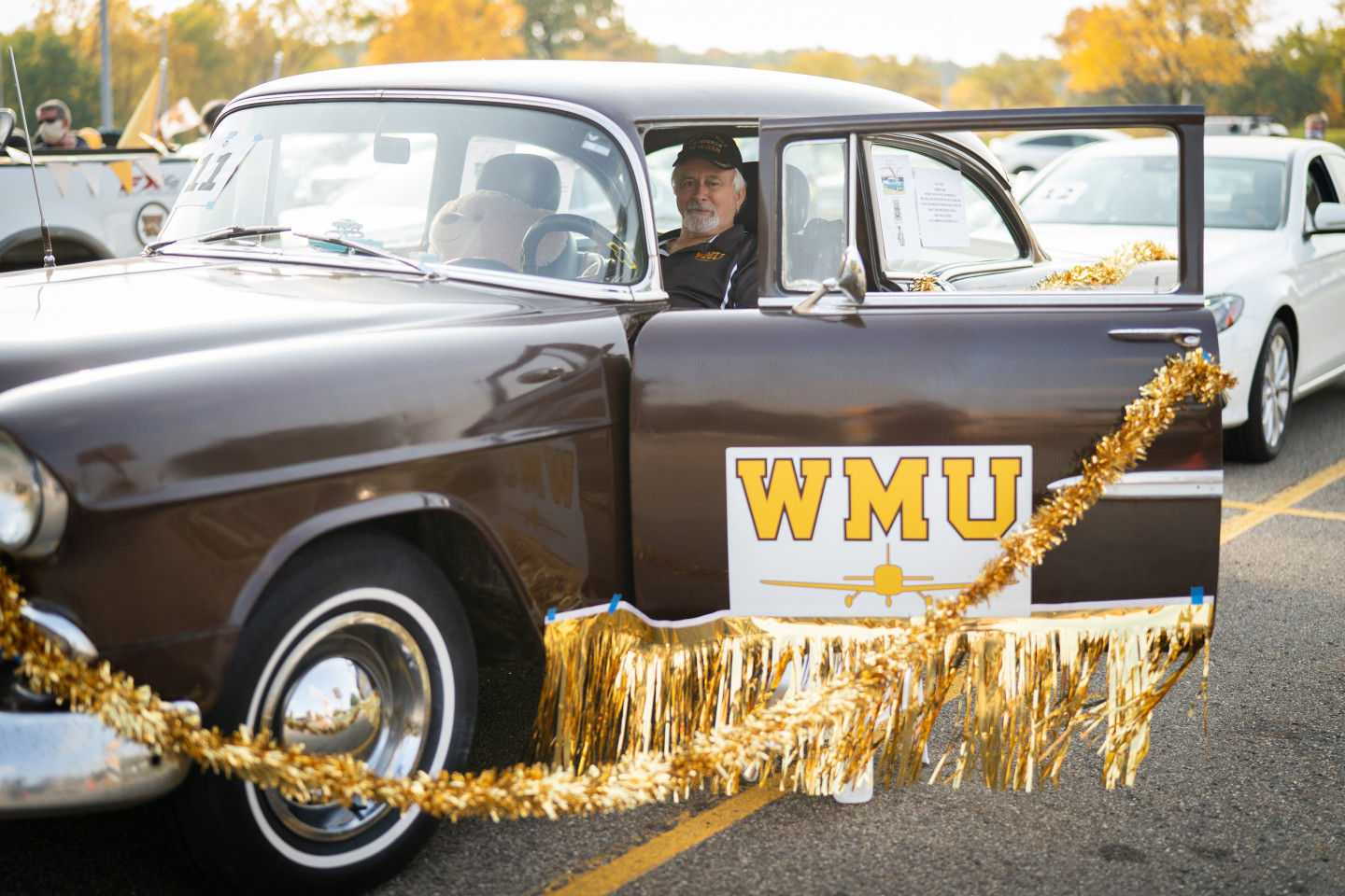 A person sits in a vintage car decorated with gold garland.