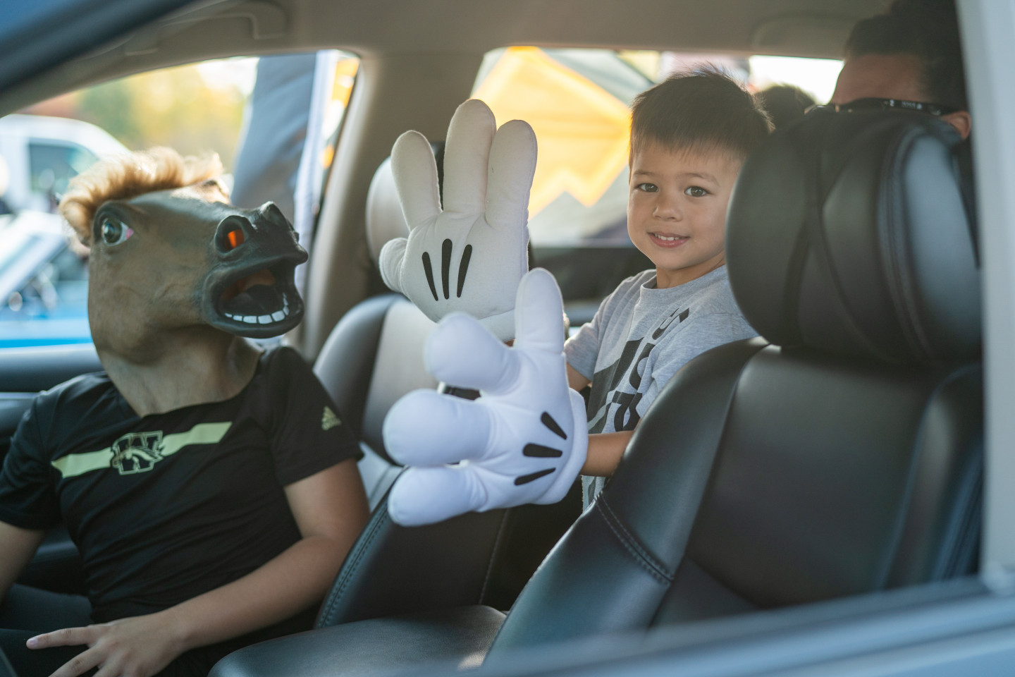 A young Bronco fan wearing large Mickey Mouse gloves.