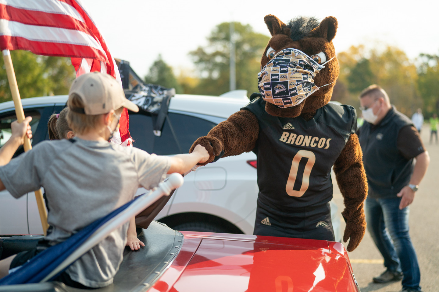 Buster Bronco bumps fists with a young fan.