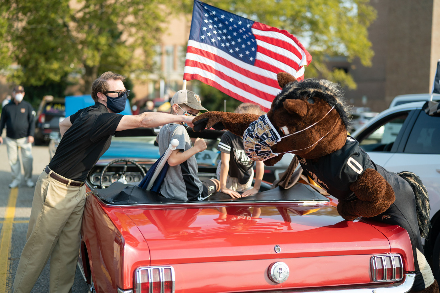 Buster Bronco bumps fists with a person during the parade.