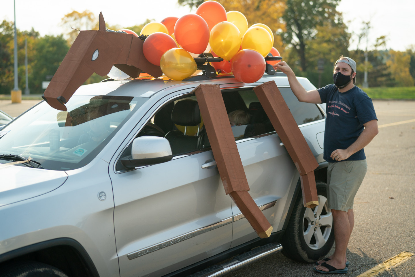 A car is decorated with a large Bronco and balloons.