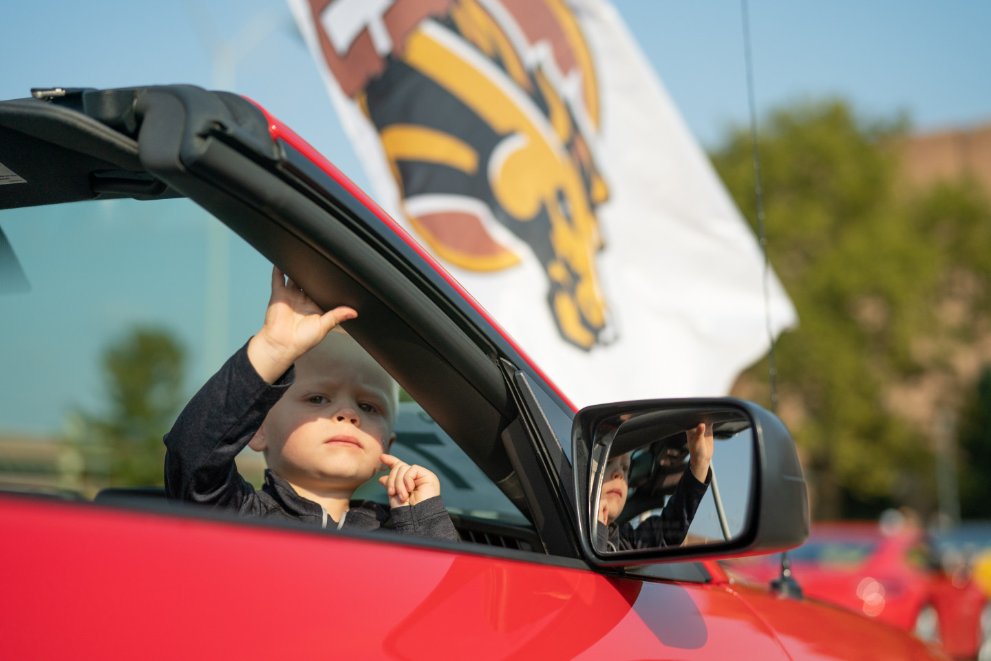 A child sits in a convertible.