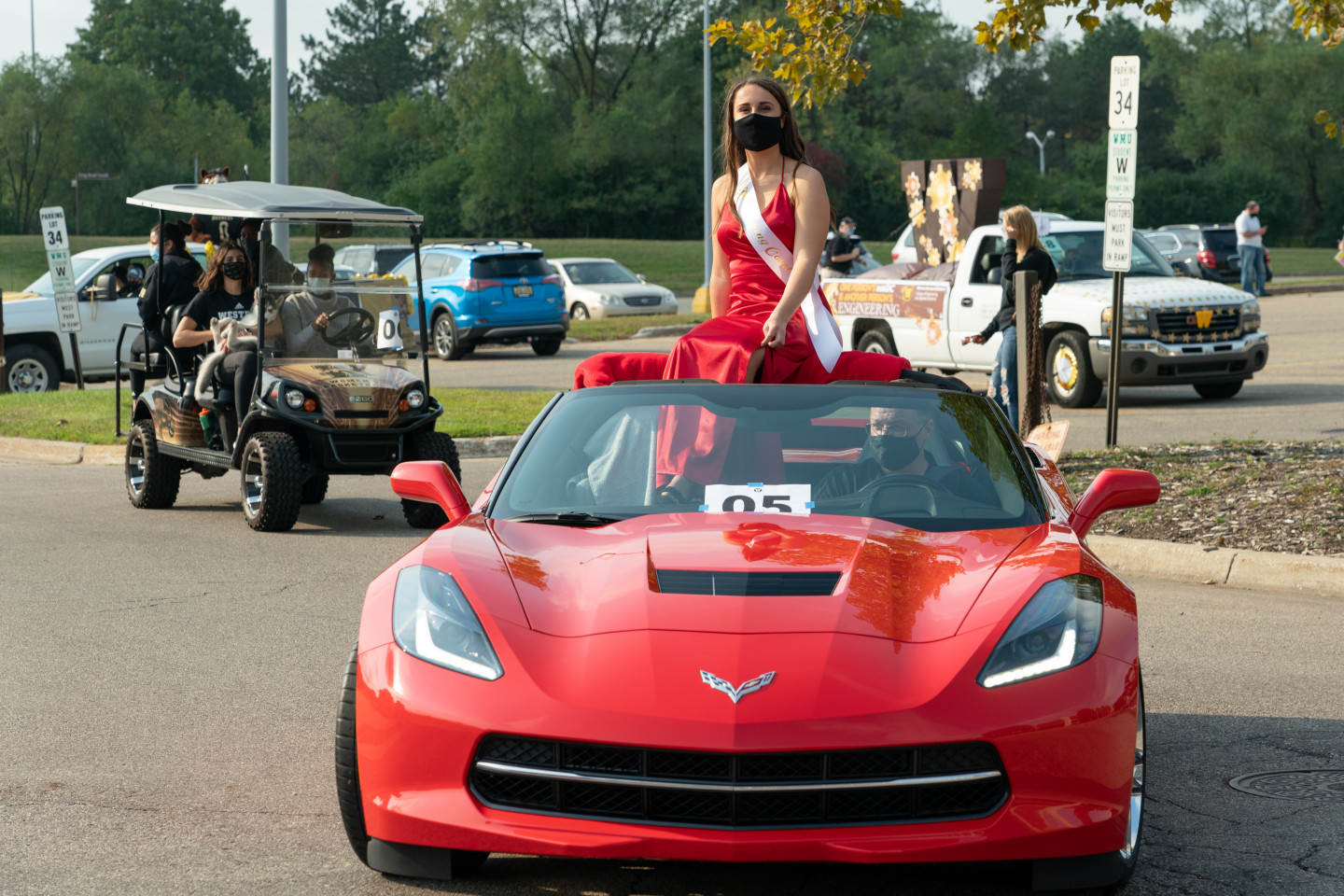 A member of the Homecoming Court rides in a convertible.
