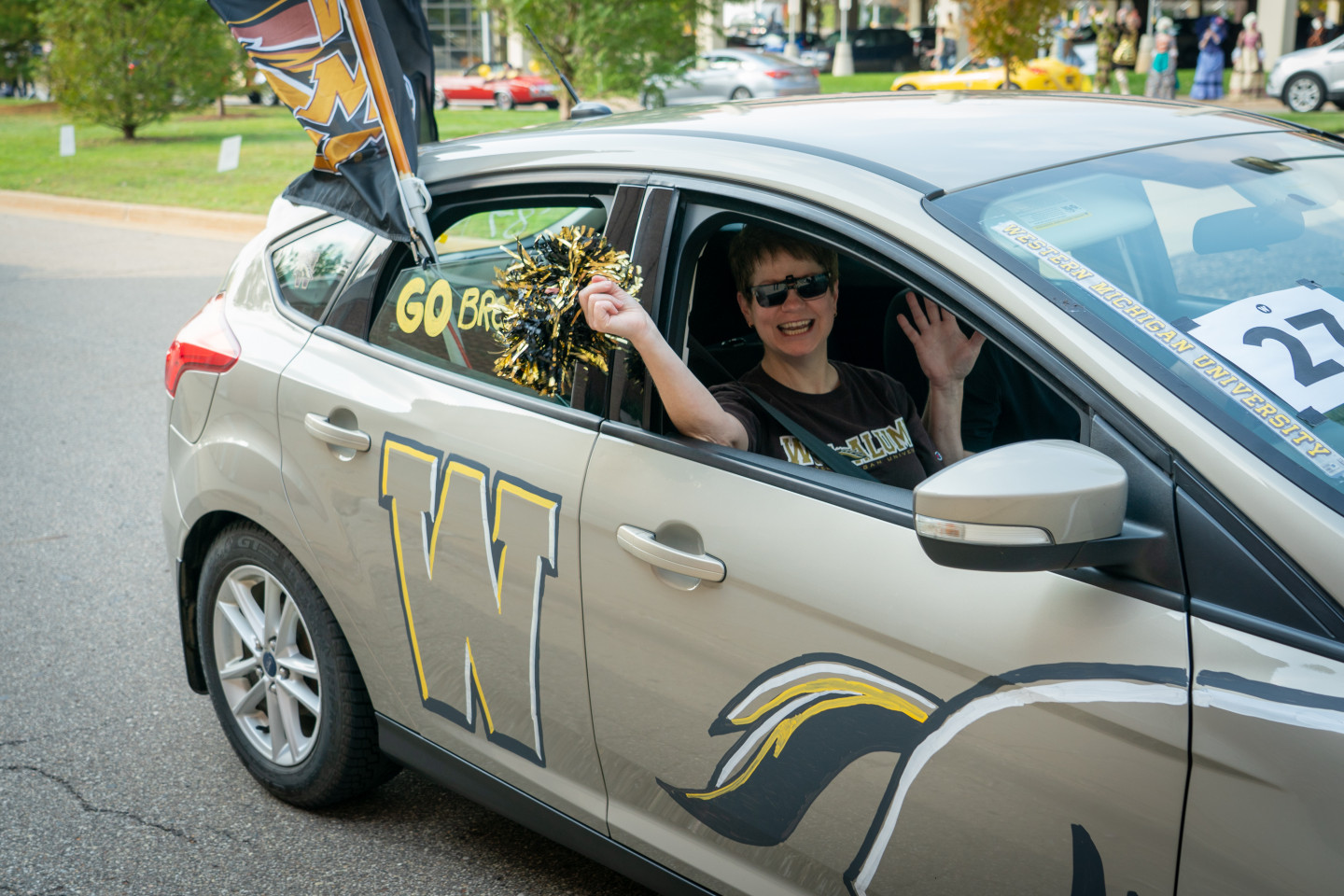 A passenger waves out the window of a car decorated in WMU spirit.