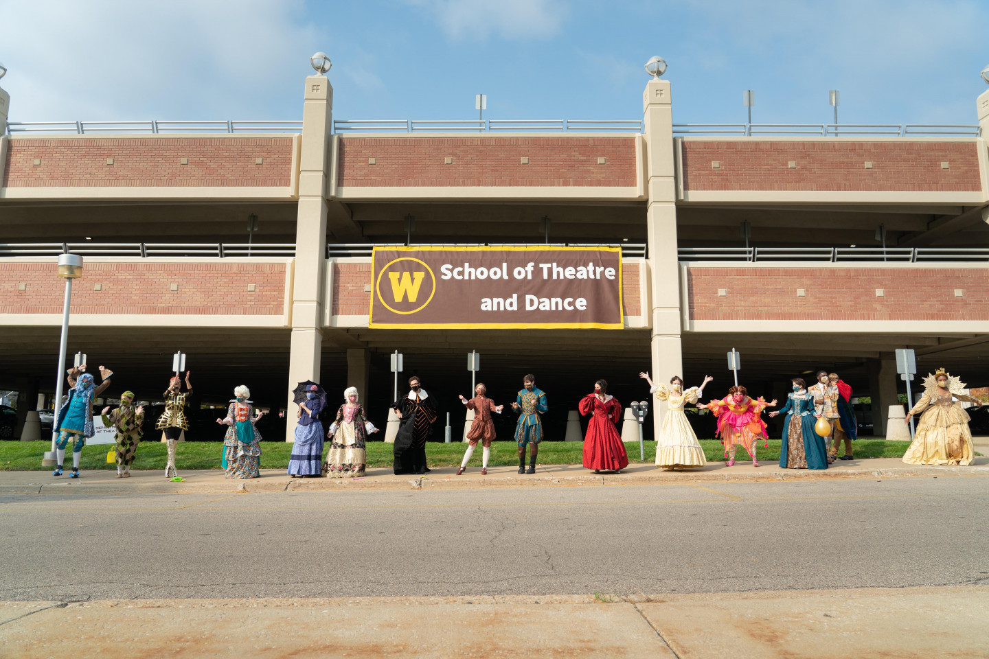 WMU Theatre students stand in front of a School of Theatre and Dance banner.